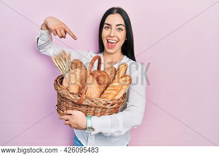 Beautiful woman with blue eyes holding wicker basket with bread smiling happy pointing with hand and finger