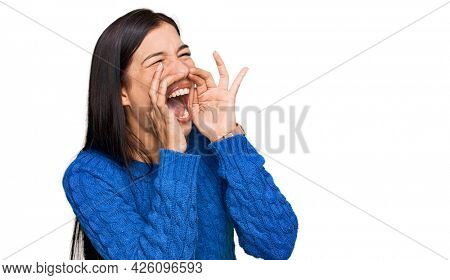 Young hispanic woman wearing casual clothes shouting angry out loud with hands over mouth