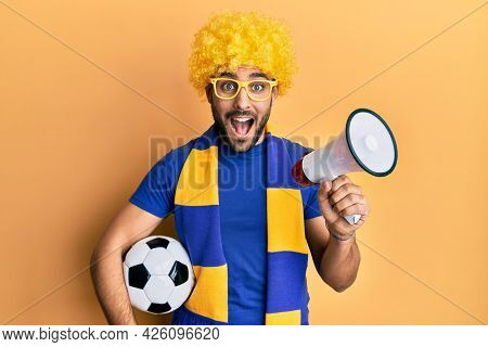 Young hispanic man football supporter holding soccer ball using megaphone smiling and laughing hard out loud because funny crazy joke.