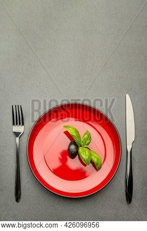 Diet. Small Amount Of Food On The Plate. One Olive Is In A Red Plate, A Knife And A Fork. Weight Los