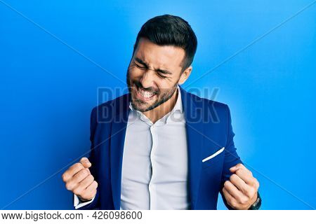 Young hispanic businessman wearing business jacket excited for success with arms raised and eyes closed celebrating victory smiling. winner concept.