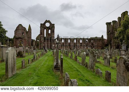 Arbroath, Scotland - August 11, 2019: Cemetery, Gravestones And Red Brick Ruins Of Medieval Arbroath