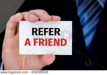 Refer A Friend. Man Holding A Card With A Message Text Written On It