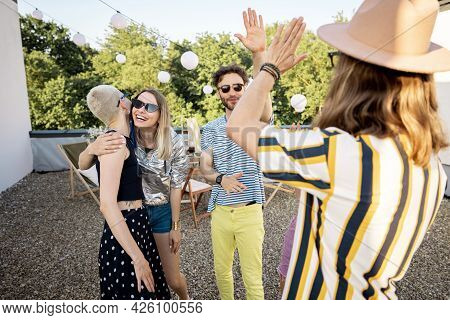 Young Stylish Friends Greets, Hugging Each Other Tightly While Gathering On A Party Outdoors. Two Hi