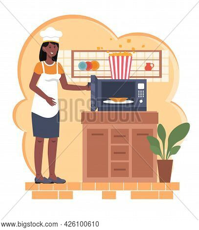 Cooking Popcorn At Home. A Woman In An Apron And A Chefs Hat Is Standing Next To The Microwave And P