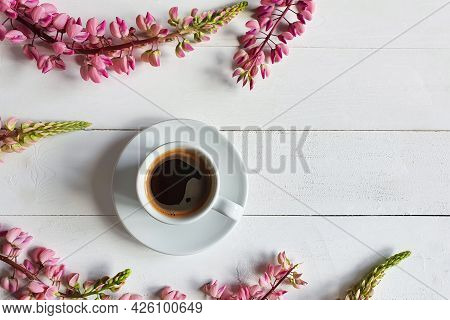 Coffee Cup And Pink Lupine Flowers On Board White Wooden Background. Place For Your Text And Product