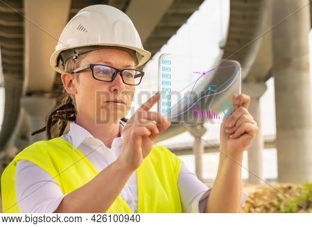 Female Engineer Or Inspector At Bridge Construction Site Working On Futuristic Gadget Analyzing Data
