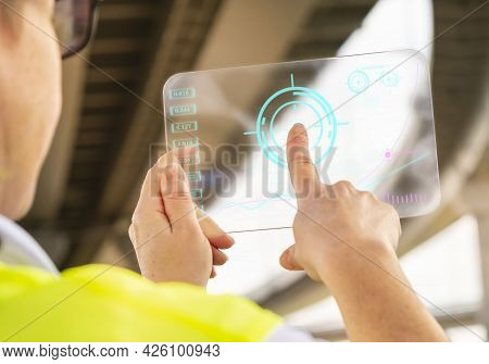 Engineer Or Inspector Uses Futuristic Tablet While Working On Road Bridge Construction Site.