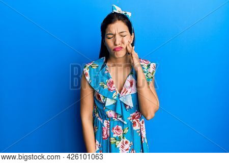 Young latin woman wearing casual clothes touching mouth with hand with painful expression because of toothache or dental illness on teeth. dentist