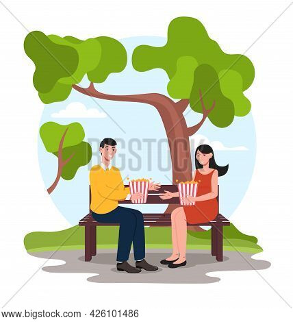 People Eat Popcorn. A Man And A Woman Are Sitting On A Bench In The Park, Smiling And Holding Boxes