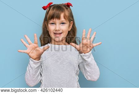 Little caucasian girl kid wearing casual clothes showing and pointing up with fingers number ten while smiling confident and happy.