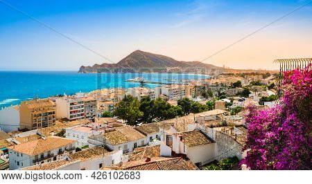 Altea, Spain - Beautiful Village With White Houses, Pink Flowers, Beach, Harbour And Mountains At Su