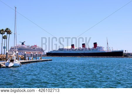July 6, 2021 In Long Beach, Ca:  Sailboat Docked On A Pier With A Modern Cruise Ship And The Histori