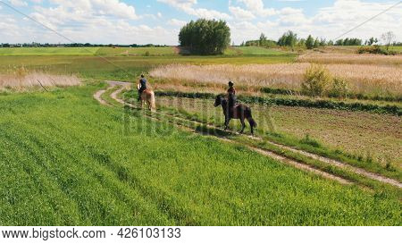 Aerial Shot Of Two Horse Riders In A Beautiful Field Meadows During The Daytime. Horse Riders Wearin