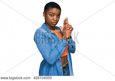 Young african american woman wearing casual clothes holding symbolic gun with hand gesture, playing killing shooting weapons, angry face