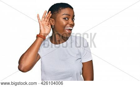 Young african american woman wearing casual white t shirt smiling with hand over ear listening an hearing to rumor or gossip. deafness concept.