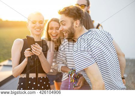 Young Stylish Friends Have Fun, Showing Something On Phone And Laugh Outdoors. Hipsters, Millennials