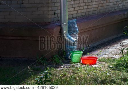 A Bucket, Once And Other Means Of Collecting Water Stand Near The Tin Drain Pipe. Next To The Brick