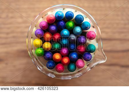 Crayons shot from above, standing in a glass container, on a rustic wooden table. Shallow depth of field for dreamy impressional feel .