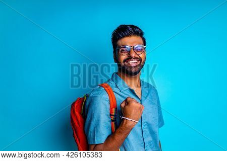Handsome Young Bearbed Indian Man With Eye Glasses In Blue Cotton T-shirt With Orange Rainbow Backpa