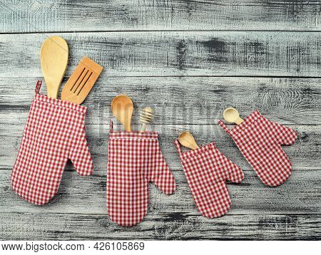 Kitchen Mittens And Kitchen Utensils On A Wooden Background. Cutlery On Wooden Backdrop. Photo For T