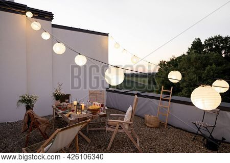 Beautifully Decorated Roof Terrace In Natural Boho Style With A Dining Table Full Of Food At Summer