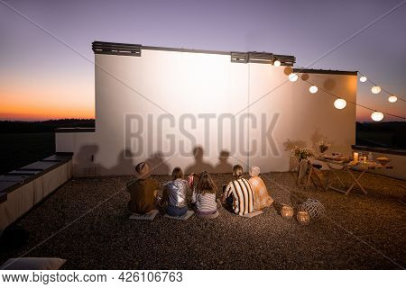 Small Group Of People Watching Movie On The Rooftop Terrace At Sunset. Open Air Cinema Concept. Whit