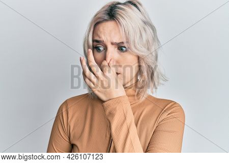 Young blonde girl wearing casual clothes smelling something stinky and disgusting, intolerable smell, holding breath with fingers on nose. bad smell