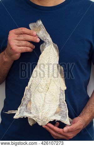 Dry Salted Cod Fish In Hands Man