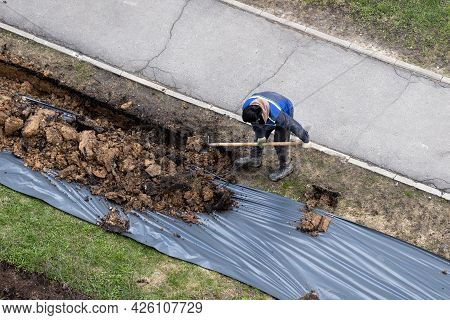 A Worker Digging A Ditch Along A Pavement In Summer.