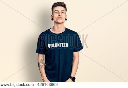 Young caucasian boy with ears dilation wearing volunteer t shirt looking at the camera blowing a kiss on air being lovely and sexy. love expression.