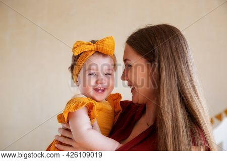 One-year-old Daughter In Yellow Clothes In The Arms Of A Loving Mother, Studio Photo For A Year Of T