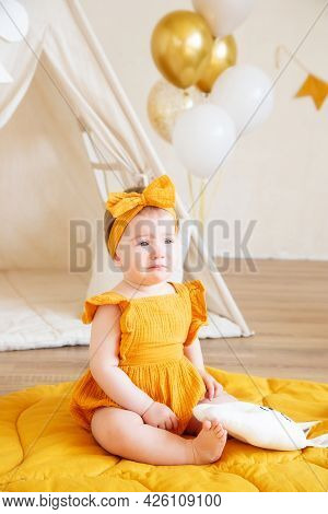 A One-year-old Caucasian Girl In Yellow Clothes Is Upset And Crying, Studio Photo For A Year Of A Ch