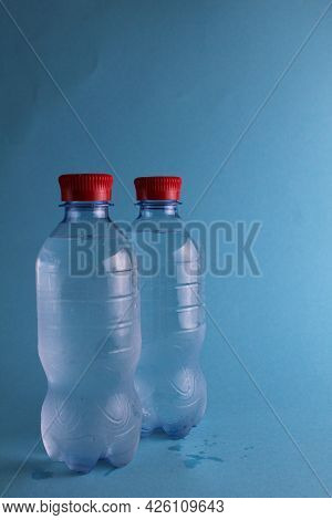 Drinking Mineralated Water In Plastic Bottles On A Blue Background With A Place For Text And With A
