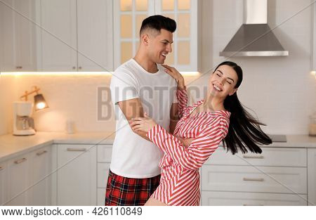Happy Couple Wearing Pyjamas And Dancing In Kitchen