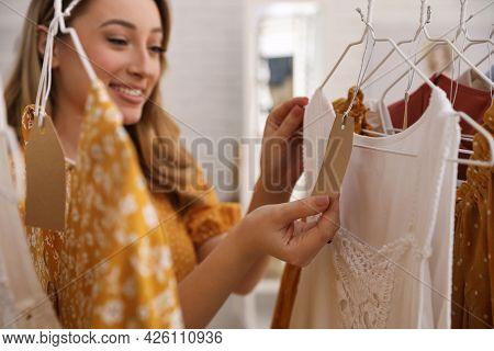 Woman Choosing Dress To Buy In Showroom, Focus On Hand