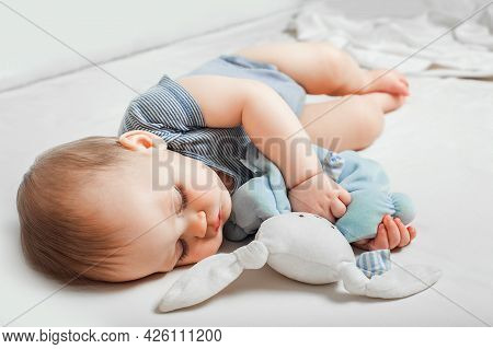 Baby With Toy In Hands Sleeps On Bed. Infant Development Concept, Toddler Restful Sleep, Teething, C