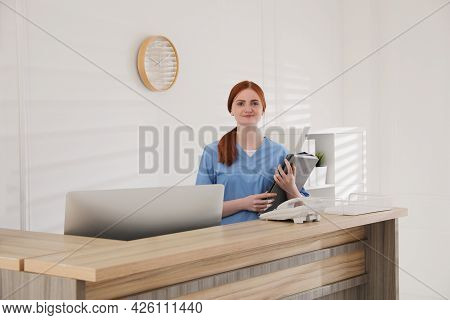 Receptionist With Document Cases At Countertop In Hospital