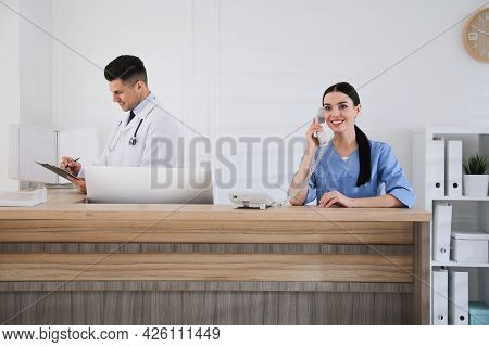 Receptionist And Doctor Working At Countertop In Hospital