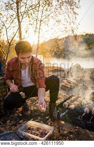 The Couple Is Resting In Nature. Man Preparing Barbecue In Nature