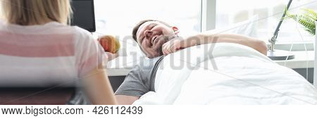 Relative Visiting Patient In Hospital Ward. Man Lying In Bed