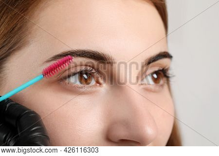 Beautician Brushing Woman's Eyebrows After Tinting On Grey Background, Closeup