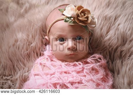 Cute Newborn Baby Girl With Floral Headband Lying On Fuzzy Rug, Top View
