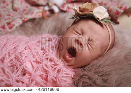 Cute Newborn Baby Girl With Floral Headband Lying On Fuzzy Rug, Closeup