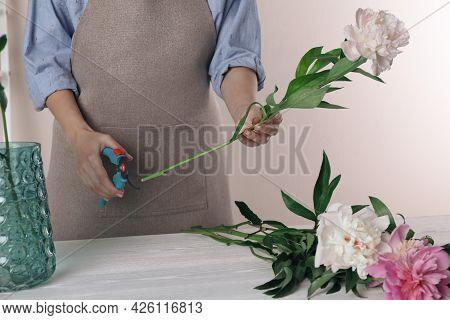Florist Cutting Flower Stem With Pruner At Workplace, Closeup