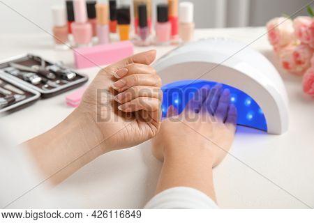 Woman Using Ultraviolet Lamp To Dry Gel Nail Polish At White Table, Closeup
