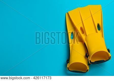 Pair Of Yellow Flippers On Light Blue Background, Flat Lay. Space For Text