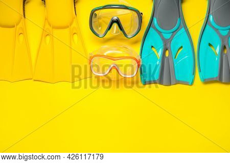 Different Flippers And Masks On Yellow Background, Flat Lay. Space For Text