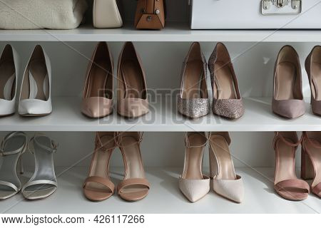 Different Stylish Women's Shoes On Shelving Unit