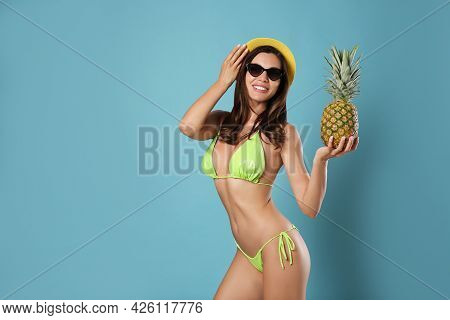 Beautiful Woman In Stylish Bikini With Pineapple On Blue Background. Space For Text